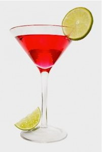 Isolated red cocktail with lime slice garnish and lime wedge